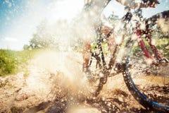 山骑自行车的人骑马通过一个肮脏的水坑 免版税图库摄影