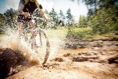 山骑自行车的人骑马通过一个肮脏的水坑 图库摄影