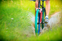 山骑自行车的人骑马通过一个肮脏的水坑 免版税库存图片