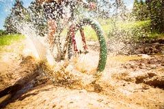 山骑自行车的人骑马通过一个肮脏的水坑 免版税库存照片