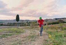 山骑自行车的人骑马通过托斯坎风景 免版税图库摄影