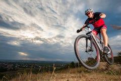 山骑自行车者反对蓝色晚上天空的骑马donwhill 库存图片