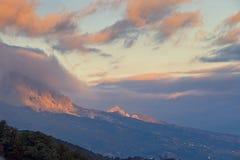 山,在云彩的天空的全景在日落的 库存照片