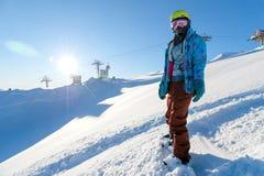 山ELBRUS,俄罗斯- 2017年11月30日:穿太阳面具和围巾的雪板女孩是在倾斜的立场 的treadled 库存图片