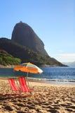 山Sugarloaf阳伞和椅子在红色海滩(普腊亚 免版税库存照片