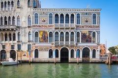 300岁从重创的运河的威尼斯式宫殿门面 免版税库存照片