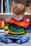 2岁使用一台数字式片剂计算机的男孩 免版税库存图片