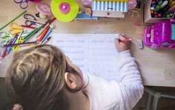 6岁做儿童的女孩写家庭作业在她的屋子里 图库摄影