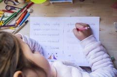 6岁做儿童的女孩写家庭作业在她的屋子里 免版税图库摄影
