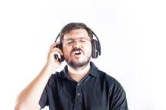 30岁唱大声的歌曲的白种人人和听从耳机的音乐 免版税库存照片