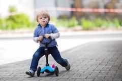 2岁在他的第一辆自行车的小孩骑马 免版税库存照片