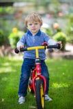 2岁在他的第一辆自行车的小孩骑马 免版税库存图片