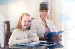 10岁女孩和她的老师 在她的专人上课期间的小女孩研究 讲解和教育概念 免版税库存图片