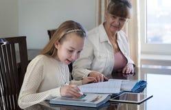 10岁女孩和她的老师 在她的专人上课期间的小女孩研究 讲解和教育概念 免版税图库摄影