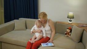 40岁有看在一种电子片剂的婴孩的母亲照片 股票视频