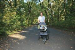 30岁有走在的婴儿推车的人 免版税库存图片