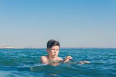 13岁男孩游泳和放松在海波浪 家庭暑假的概念 库存图片
