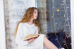 10岁画象儿童在窗口的阅读书在圣诞节 图库摄影