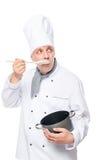 30岁的厨师新手吃与从平底锅的一把匙子 库存照片