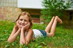12岁的女孩在草和微笑说谎 免版税库存照片