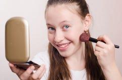 12岁的女孩得到在面颊的刷子粉末 库存照片