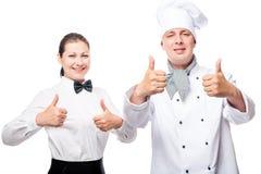 30岁的女服务员和厨师显示成功的迹象反对 免版税库存照片