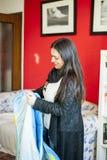 35岁的妇女在她的家叠起毯子 库存图片