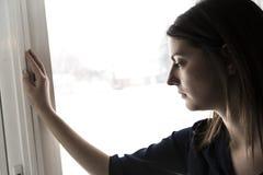 30岁的妇女在窗口前面站立 图库摄影