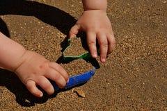 3岁的手使用与在海滩的pattypan形式的女孩 库存图片