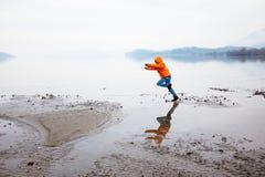 12岁的男孩沿海滩跑在冬天 库存照片