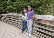 22岁的Amerasian摆在木桥的男性和他的母亲在华盛顿公园树木园,西雅图,华盛顿 免版税图库摄影