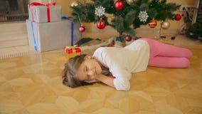 10岁睡觉在圣诞树下的女孩在早晨 当前的母亲留给在地板 股票视频