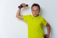 12岁画象男孩举的哑铃 库存图片