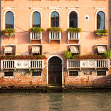 300岁从重创的运河的威尼斯式宫殿门面 免版税库存图片