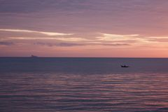 岛民用浆划一个挖掘的独木舟在日落 库存图片