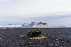 岩浆与山的岩石平原在背景中 免版税库存照片
