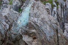 岩溶的岩石特写镜头与鱼网的遗骸的 免版税库存图片