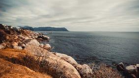 岩石、山和海洋有云彩的 免版税库存图片