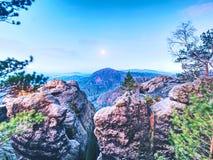 岩石与树 在一座美丽的山的满月夜 从雾和小山增加的砂岩峰顶 免版税库存照片