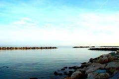 岩石包围的光滑的亚得里亚海在天蓝色的天空下 免版税图库摄影