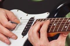 岩石吉他弹奏者在电吉他特写镜头上把弦的手指放 图库摄影