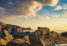 岩石和大厦在海日落的 里窝那,托斯卡纳rivie 免版税库存照片