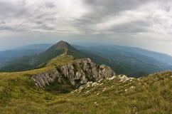岩石和峭壁在迁徙道路的黑暗的云彩下在苏瓦Planina山 免版税图库摄影