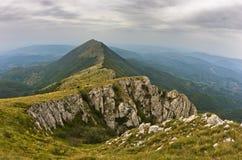 岩石和峭壁在迁徙道路的黑暗的云彩下在苏瓦Planina山 免版税库存照片