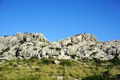 岩石和明白蓝天和绿草 免版税图库摄影