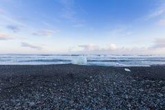 黑岩石和沙子使海岸线冬天季节风景靠岸 库存图片