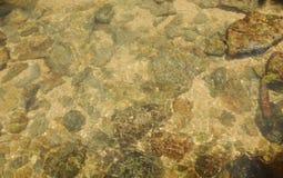 岩石和沙子在河用清楚的水研了 免版税库存照片