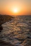 岩石和波浪在日落 图库摄影