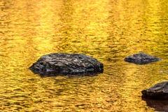 岩石和金子秋天湖反射 图库摄影