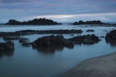 岩石喜怒无常的长的曝光沿海滩的 库存图片